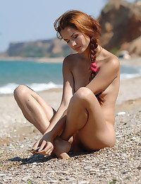 Pretty young girl takes her pink swim-suit off coupled with poses artistically on the bonny beach.