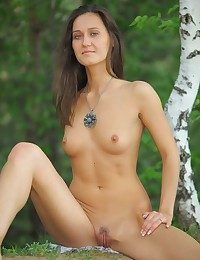 Green-eyed brunette with tanned complexion and slender build.