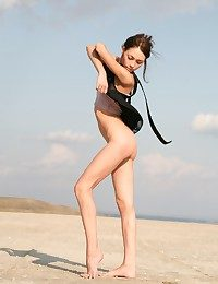 Tall skinny brunette taking not present her transparent black dress on the beach